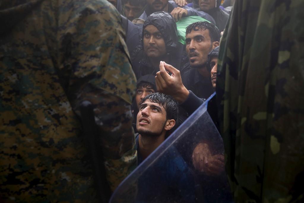 Migrantes y refugiados piden a policias macedonios que les den paso para cruzar la frontera de Grecia hacia Macedonia durante una tormenta, cerca de Idomeni. 10/09/2015